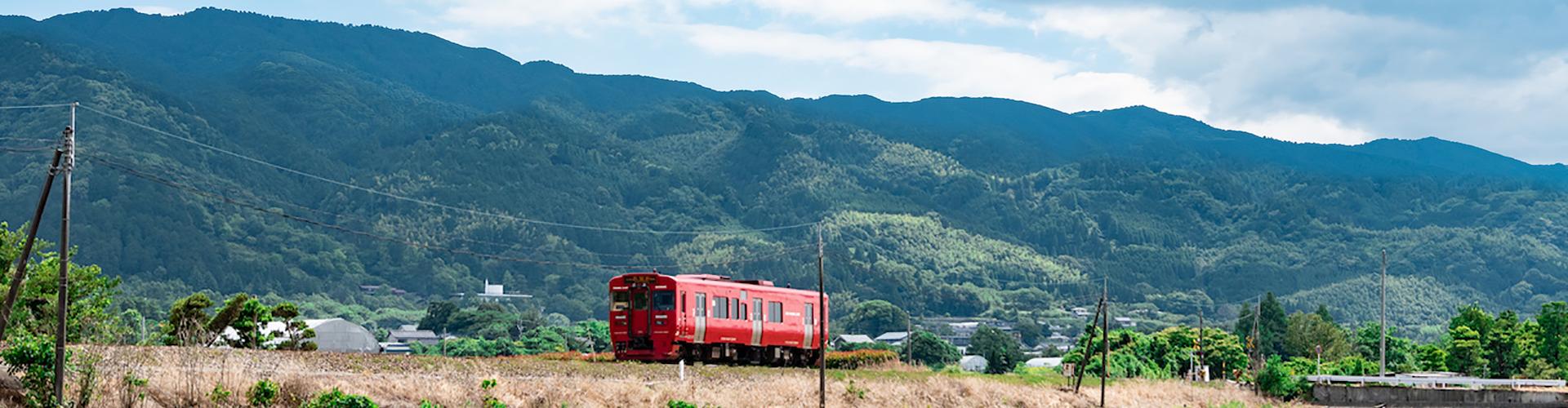 耳納連山を背景に走る久大本線の気動車